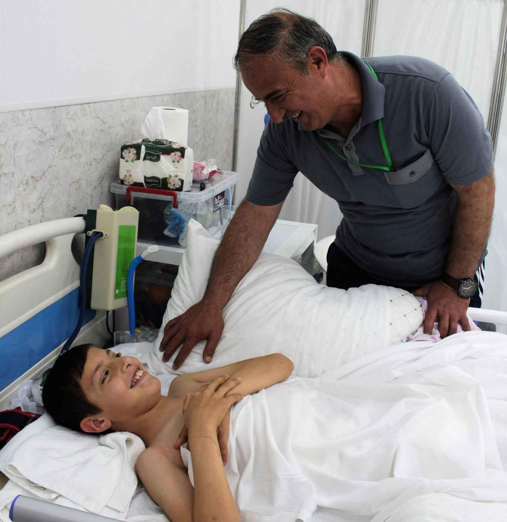 Rayyan (12 years old), war victim, it the Emergency Hospital ward. His father is near him.