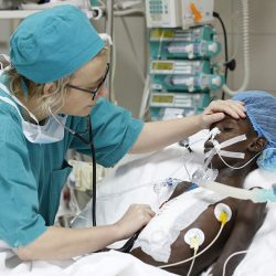 Staff visiting a patient in the ICU of the Salam Centre for Cardiac Surgery, Khartoum