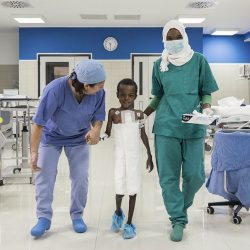 A child walks with a doctor and a nurse in a ward at the Salam Centre for Cardiac Surgery in Khartoum, Sudan