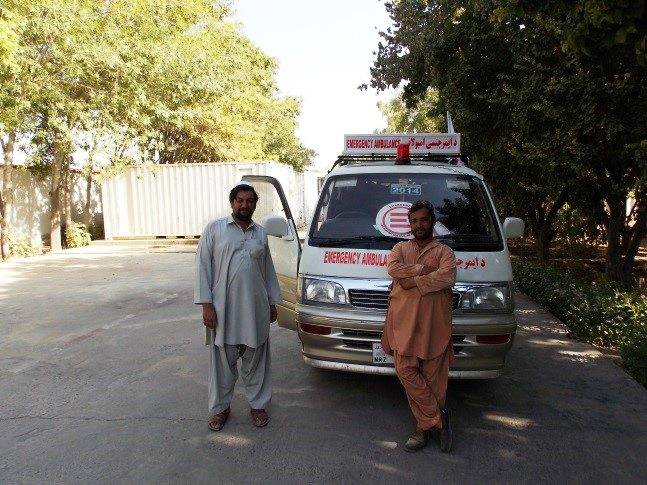 Aziz and Nabi near an EMERGENCY ambulance