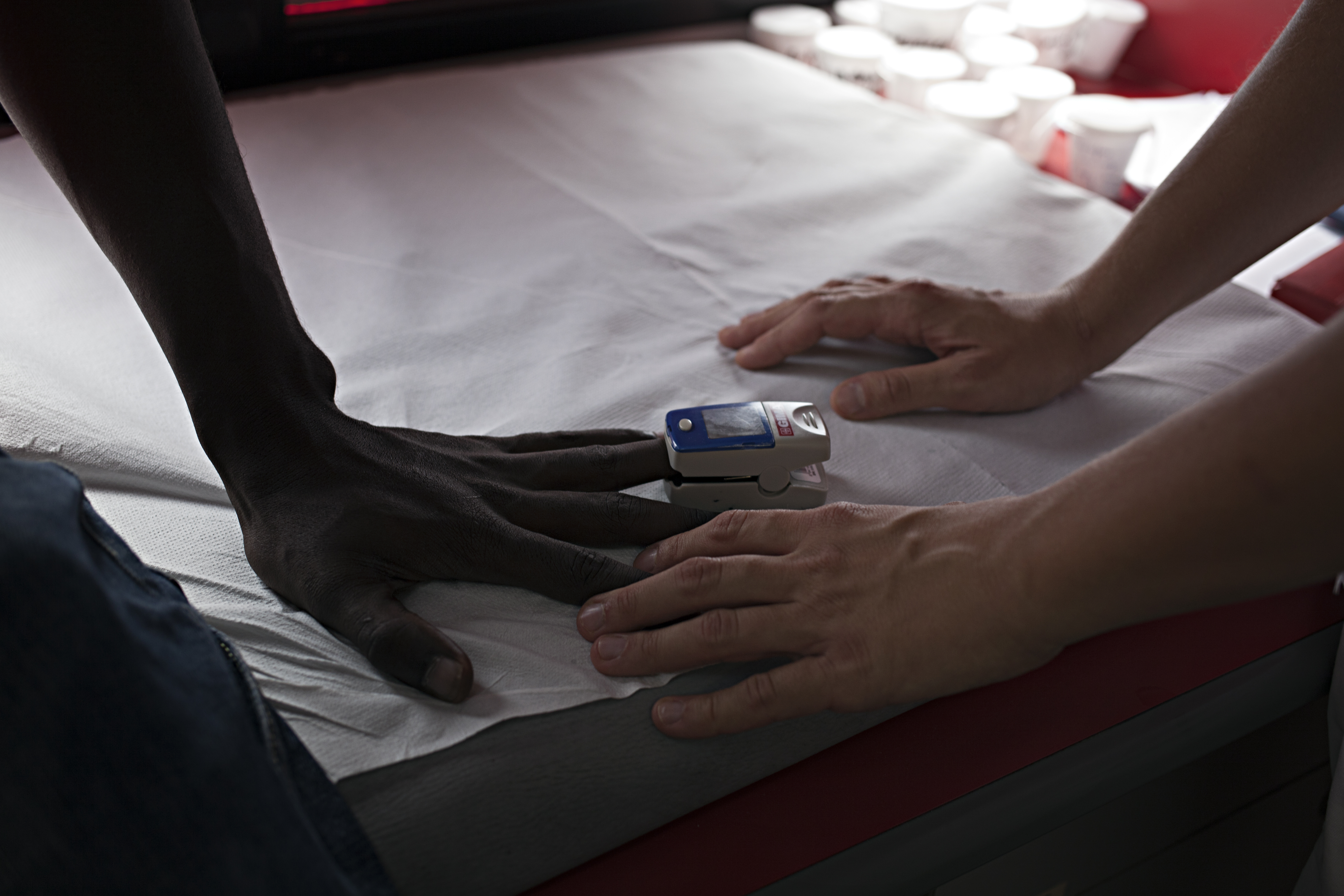 The hand of a patient and that of a member of EMERGENCY staff