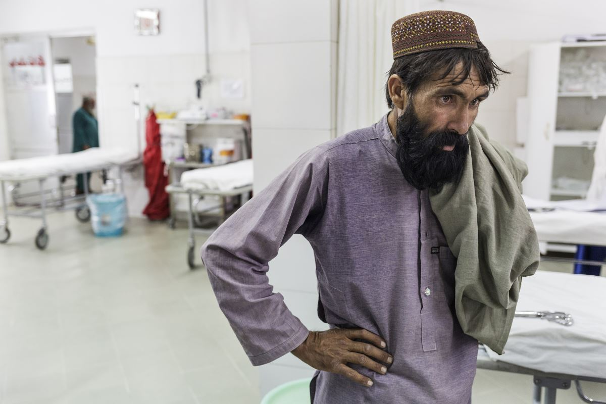 Khudai Noor's father watching the medical staff helping his son
